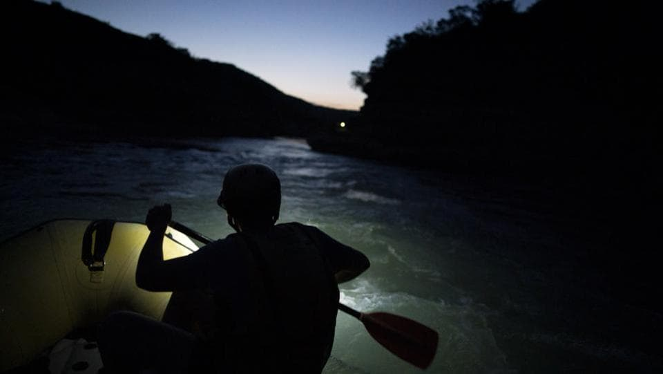"A river rafting guide paddles at dusk. ""It's like humans,"" said Elton Pashollari, a river rafting guide whose clients are increasingly attracted by the Vjosa's wildness. ""What happens if one of your arteries, it stops, blood doesn't circulate anymore? It's the same thing with the Vjosa."" (Felipe Dana / AP)"
