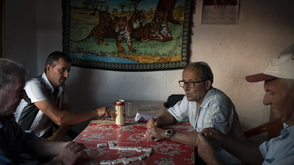 Residents play dominoes in a small bar in the village of Kute, Albania. Dozens of residents from the village joined nonprofit organizations to file what was Albania's first environmental lawsuit against the construction of a dam in the Pocem gorge. They won in 2017, but the government has appealed. Relieved by their victory, they now wait anxiously for the outcome of the government's appeal. (Felipe Dana / AP)