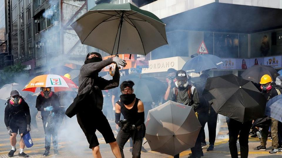 An anti-government demonstrator throws back a tear gas canister during a protest march in Hong Kong, October 20.