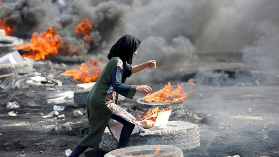 A demonstrator runs between burning tires during a curfew, two days after the nationwide anti-government protests turned violent, in Baghdad, Iraq.