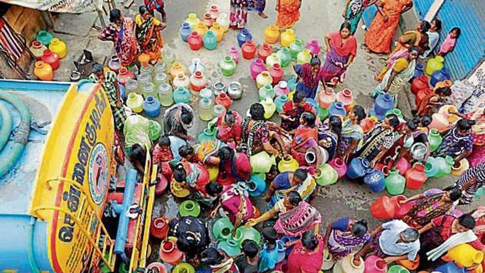 Locals stand in queues to fill vessels filled with drinking water from a water tanker in Chennai.