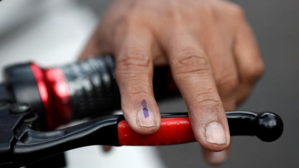 A man's inked marked finger is seen as he leaves a polling station on his bike after casting his vote during Maharashtra state elections in Mumbai.