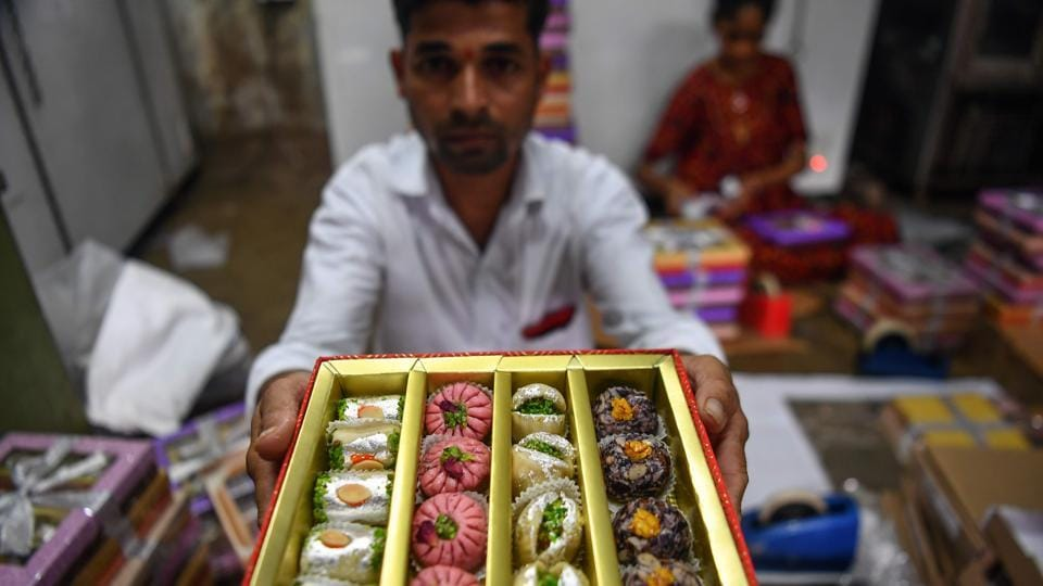 "A worker holds up a gift box of sweets being packed at a factory in Mumbai. ""The joy of opening wrappers to find surprising items has been replaced with the usual sweets... which has taken the sheen off the festival somewhat…I am not sure if there will be many gifts coming my way this year,"" said finance executive Chakraborty. (Indranil Mukherjee / AFP)"