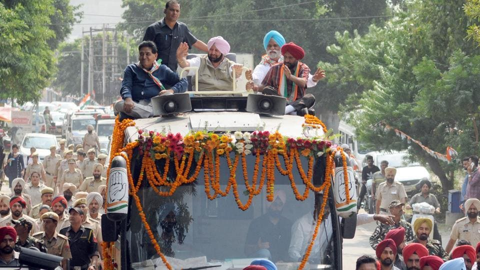 Punjab Chief Minister Capt Amarinder Singh with Congress candidate Balwinder Singh Dhaliwal (R) during a road show ahead of bypoll elections in Phagwara, Punjab.