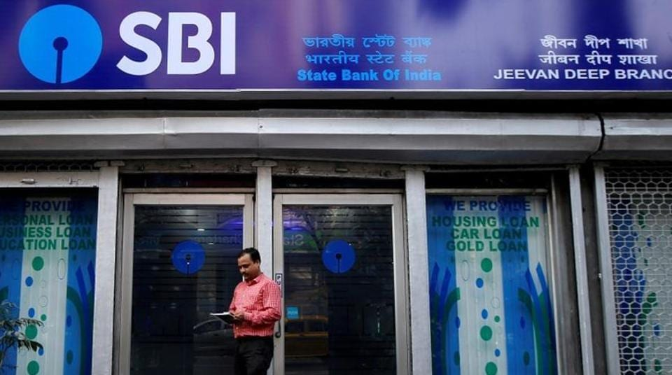 A man checks his mobile phone in front of State Bank of India (SBI) branch in Kolkata.