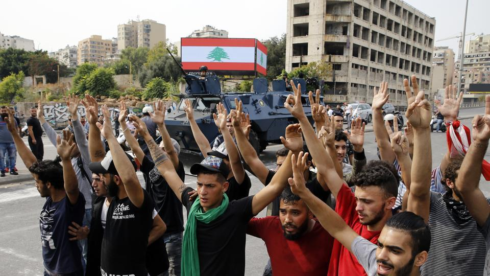 Anti-government protesters raise their hands as police disperse them from main highway in Beirut, Lebanon, Saturday, Oct. 26, 2019. The removal of the roadblocks on Saturday comes on the tenth day of protests in which protesters have called for civil disobedience until the government steps down. (AP Photo/Bilal Hussein)