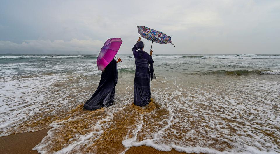 Women stand along the shore of Marina beach, in Chennai, on October 21. Heavy rains have been lashing several parts of south India as the North East monsoon turned active this week. Karnataka and Kerala are battling floods as rivers flowing through the states have swelled up after heavy downpour in the region, prompting an orange alert by the MeT department . (PTI)