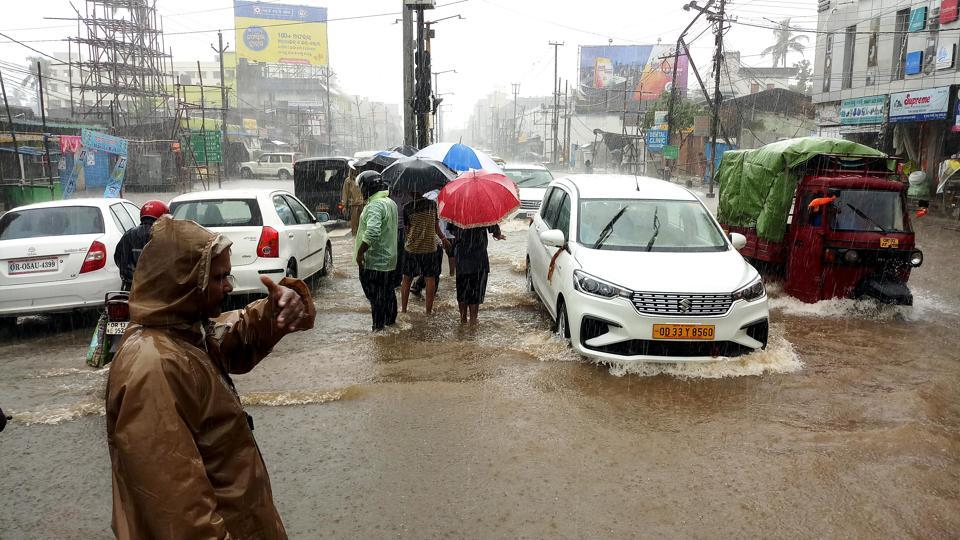 Vehicles passing through a waterlogged road following heavy rainfall in Bhubaneswar.