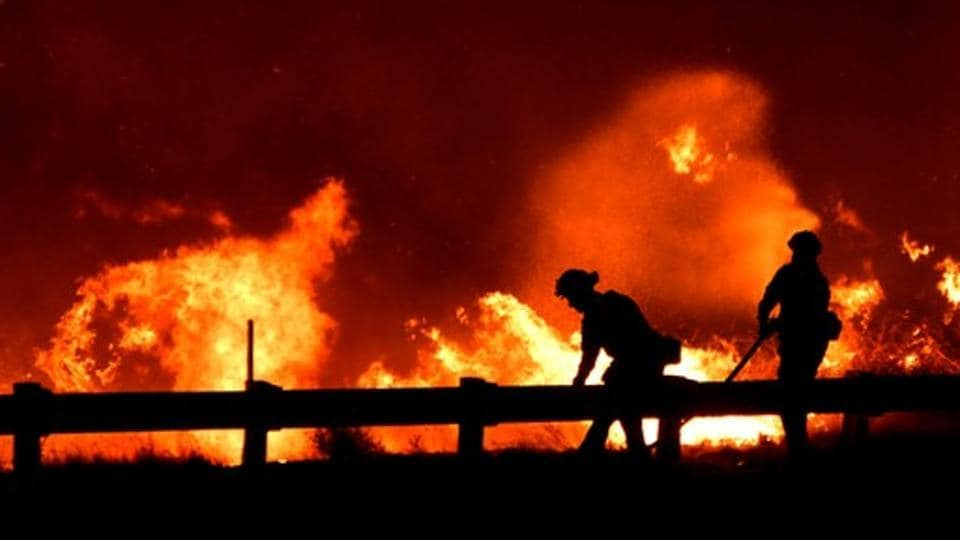 Firefighters battle a fire, as a wind driven wildfire continues to burn in Canyon Country north of Los Angeles, California.