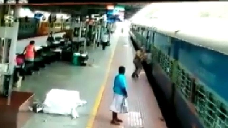 An RPF personnel - standing merely five feet away from the train - swings into action and pushes the man inside the coach.