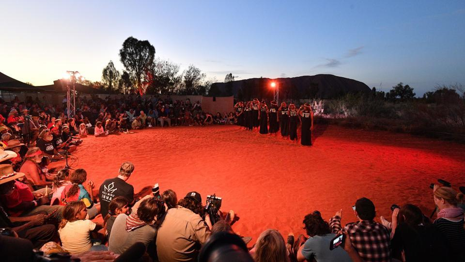 Indigenous Anangu perform a traditional dance during a ceremony marking the permanent ban on climbing Uluru, also known as Ayers Rock, at Uluru-Kata Tjuta National Park in Australia's Northern Territory. Indigenous Australians performed songs and traditional dance as the sun set over Uluru on Sunday, capping a weekend of celebrations to mark the historic ban on climbing the sacred site. (Saeed Khan / AFP)