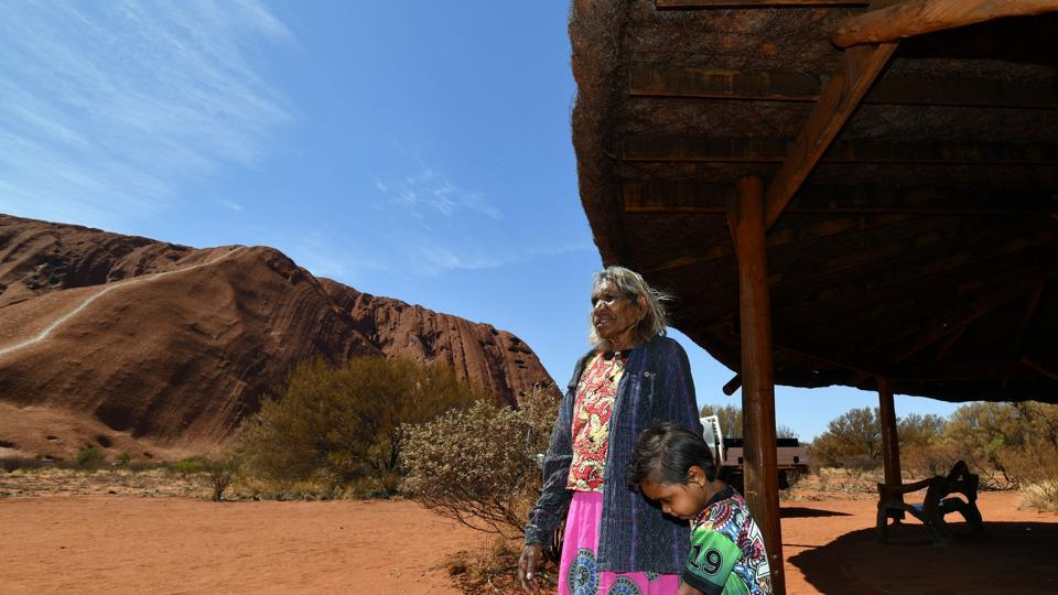 "A traditional Aboriginal owner of Uluru-Kata-Tjuta, in front of the Uluru. A crowd gathered late Friday at the base of the site to watch rangers erect the ""permanently closed"" sign, in line with the long-held wishes of indigenous Australians. ""No more climbing today,"" shouted indigenous elder Nelly Patterson. ""Close it,"" she yelled to a loud cheer from the crowd. (Saeed Khan / AFP)"