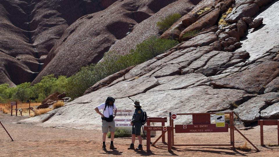 "A ranger (R) briefs a tourist (L) at the base of Uluru after the permanent ban on climbing the monolith. As well as respecting cultural practices, the ban is designed to protect the site from further environmental damage and ensure visitors' safety. ""We are all very happy, as traditional owners, that the climb is closed now, after a long fight from handback to today,"" Reggie Uluru told reporters through an interpreter on Saturday. (Saeed Khan / AFP)"