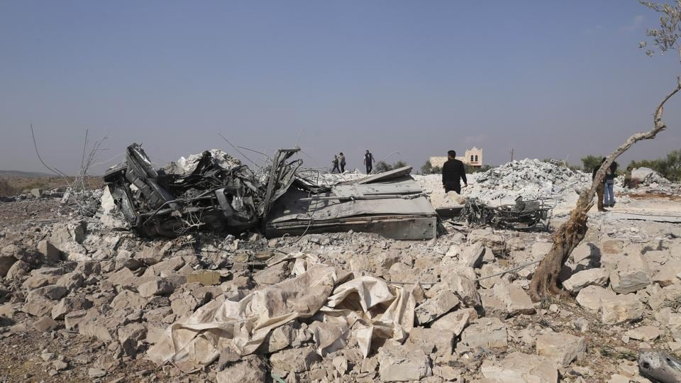 People look at a destroyed houses near the village of Barisha, in Idlib province, after an operation by the U.S. military which targeted Abu Bakr al-Baghdadi, the shadowy leader of the Islamic State.