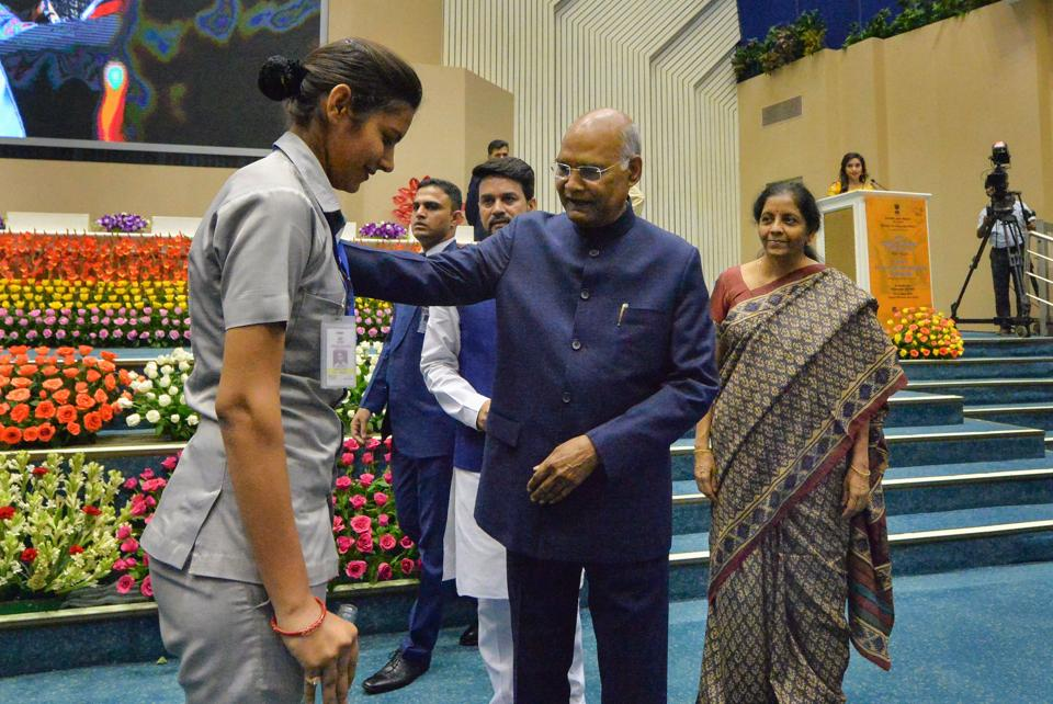 President Ram Nath Kovind interacts with a woman security staff, who slipped while standing for the National Anthem during the National Corporate Social Responsibility Awards function in New Delhi.