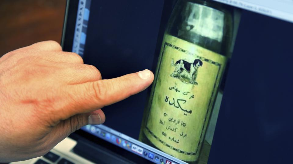 Bruce Khabbazi points to an image of an original bottle of 'Arak Saggi', or Doggy Arak, that was produced in Iran in the 1950s. Born in Shiraz to a family with more than 125 years in the food industry, Khabbazi fled Iran at age 16 to avoid fighting in the Iran-Iraq war and because he said he saw no future for young Iranians after the revolution. In Canada, he changed his name from Behrouz to Bruce. (Kamran Jebreili / AP)