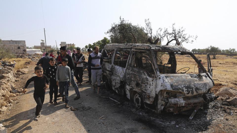 People look at a destroyed van near the village of Barisha, in Idlib province, after an operation by the US military which targeted Abu Bakr al-Baghdadi .