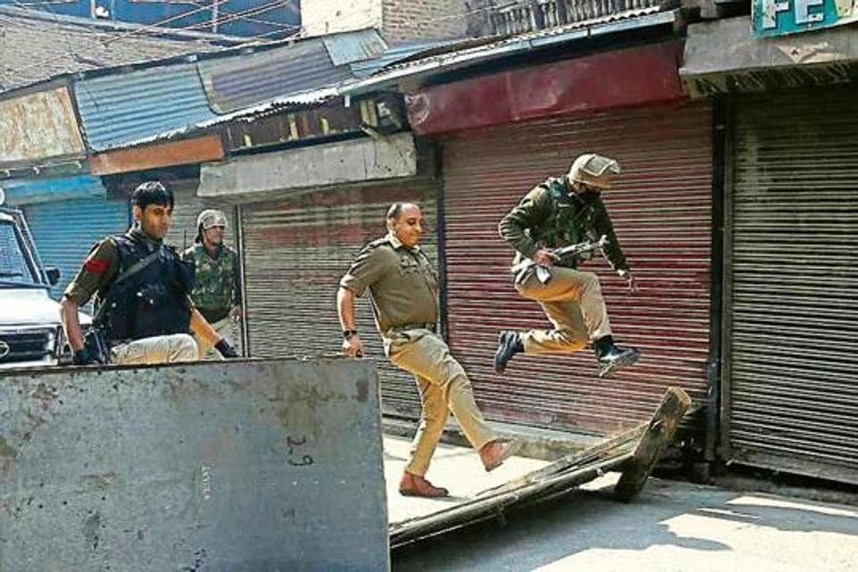 A policeman jumps as his officer kicks to remove a road block put up by protesters in Srinagar.