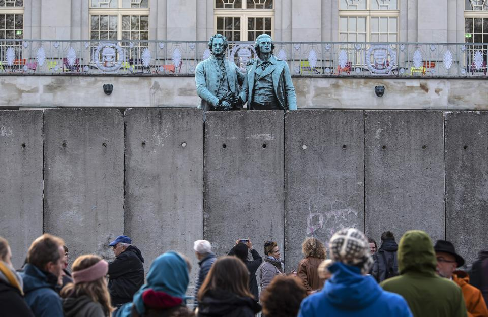 A wall, an art performance of the National Theatre Weimar, stand in front of the memorial of German poets Johann Wolfgang von Goethe, left, and Friedrich Schiller, right, prior the 30th anniversary of falling Berlin wall in Weimar, Germany, Wednesday, Oct. 30, 2019. With the temporary installation of 17 wall elements, the National Theatre recall the events of autumn 1989. The artist Christina Wildgrube designs this 'wall'. Unlike the former Belin wall, the art project should not create a long-term separation, but bring people together. (AP Photo/Jens Meyer) (AP)
