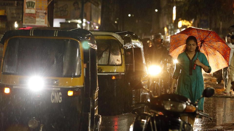 People use umbrella in heavy rain at Katraj in Pune.