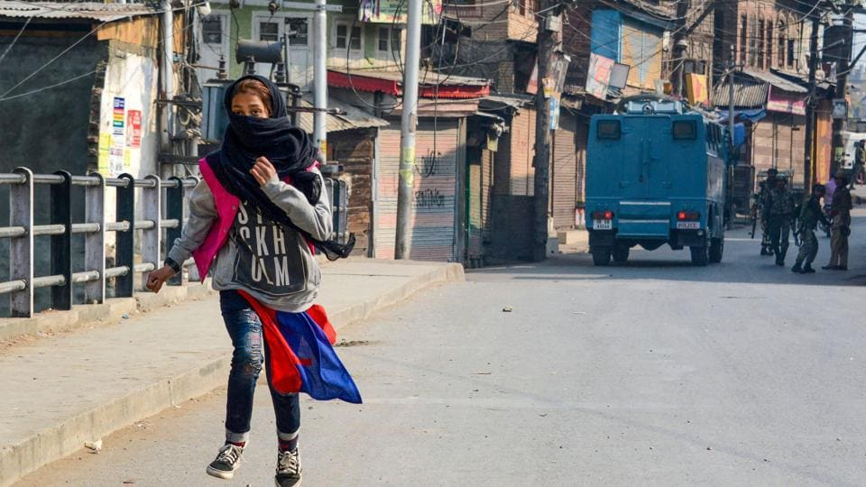 A girl runs for cover after throwing stones during a protest in Srinagar.
