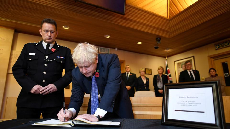 Britain's Prime Minister Boris Johnson signs a book of condolence for the 39 dead found in lorry, during a visit to Thurrock Council Offices in Grays, England. (Stefan Rousseau / Pool via REUTERS)