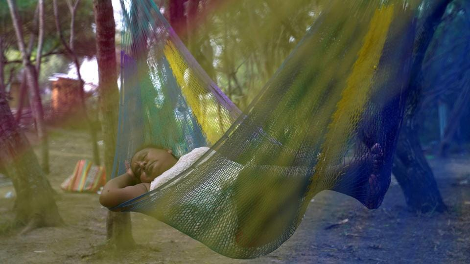 A Mexican asylum-seeking woman sleeps in a hammock in an encampment where she lives as she waits for her turn to seek asylum in the US in Matamoros, Mexico. (Veronica G. Cardenas / REUTERS)