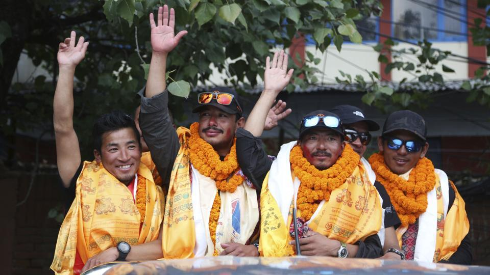 Nepalese mountaineer Nirmal Purja (2nd L), who became the fastest climber of the world's 14 highest peaks, waves to the gathering as he arrives with his team at the airport in Kathmandu, Nepal. Purja scaled the 8,027-metre Mount Shishapangma in China on Tuesday, which was the last of the 14 peaks that are more than 8,000 metres (26,240 feet) in height. (Niranjan Shrestha / AP)