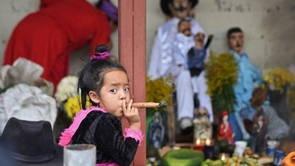 A three-year-old girl smokes a cigar during the Saint Simon celebrations in San Andres Itzapa, Guatemala. Popular belief holds that the saint helps people find work, solves family problems and cures illnesses. (Orlando Estrada / AFP)