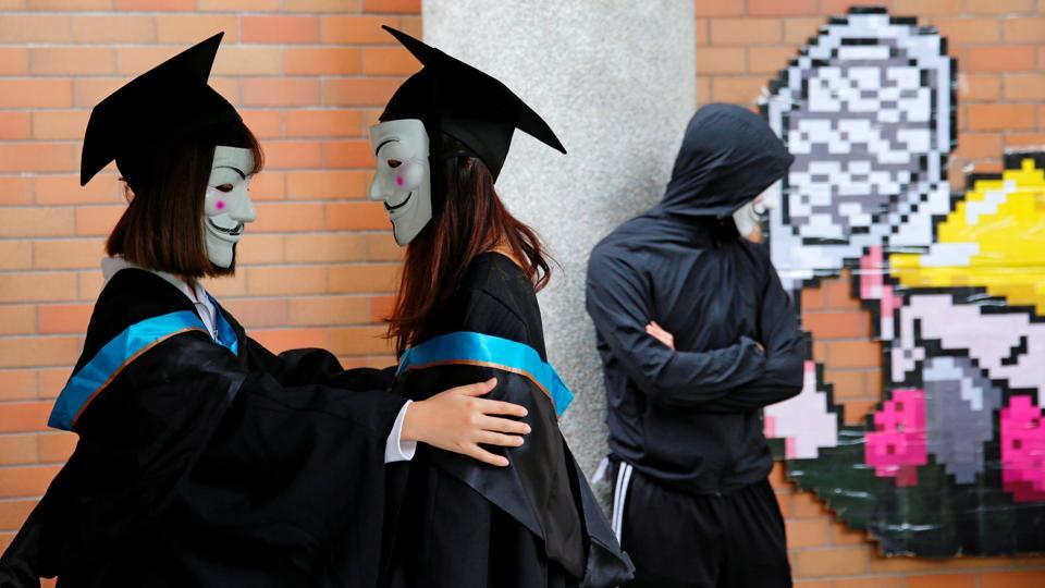 University students wearing Guy Fawkes masks pose for a photoshoot of a graduation ceremony to support anti-government protests at the Hong Kong Polytechnic University, in Hong Kong. (Tyrone Siu / REUTERS)
