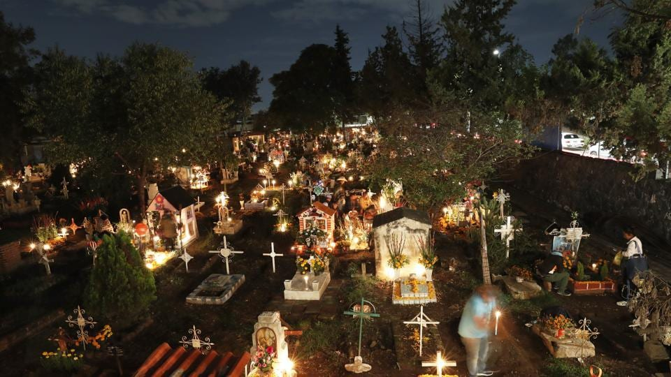 Candles illuminate children's tombs in the San Gregorio Atlapulco cemetery during Day of the Dead festivities on the outskirts of Mexico City. (AP)