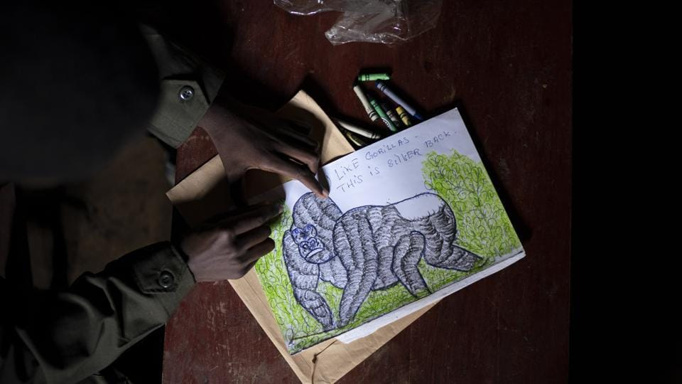 """Jean Claude Masengesho draws a silverback gorilla in Kinigi, Rwanda. He would like to someday become a tour guide, which would earn him about $320 monthly. The obstacle is that most tour guides have attended college, and the 21-year old isn't sure how his family can afford tuition. """"It's my dream, but it's very hard,"""" he says. """"In this village, every young person's dream is to work in the park.""""  (Felipe Dana / AP)"""