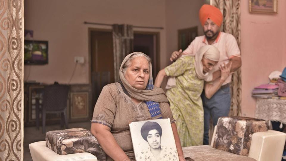 Manjit Kaur holds a photograph of her late husband Bhagat Singh, a 1984 Anti-Sikh riot victim, in the presence of her mother-in law Kirpal Kaur and brother-in law Harcharan Singh, in Ludhiana, Punjab. November 01 marked the 35th anniversary of 1984 Anti-Sikh riot. (Gurpreet Singh / HT Photo)