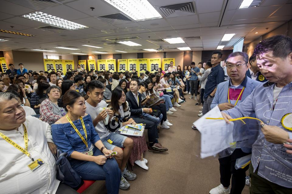 Prospective buyers gather to try and purchase a home at the sales office for the One Eighty residential property, developed by Three Tops Ltd., in Hong Kong.