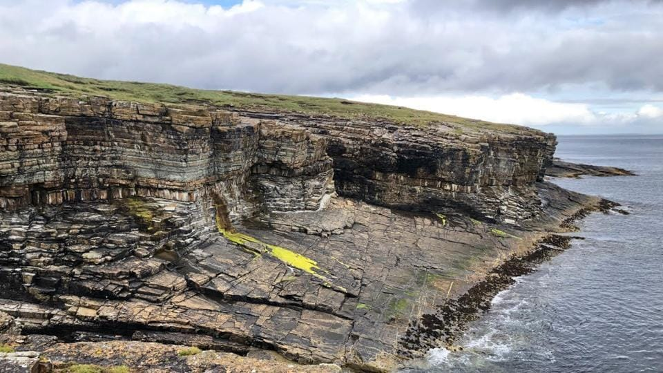 The lichen-covered cliffs of the Orkney landscape.