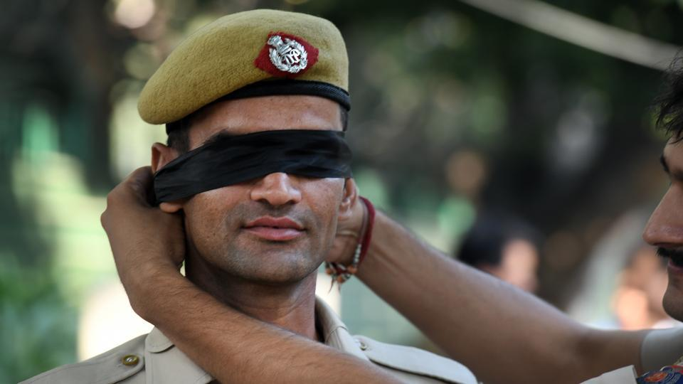 A Delhi Police personnel is seen blindfolded during a protest outside the Delhi Police headquarters, at ITO, in New Delhi. Thousands of police personnel protested outside the Delhi Police headquarters on Tuesday in an unprecedented public demonstration of anger over an assault on members of the force by lawyers after a violent clash on the weekend, and to express their resentment at senior officers for not rising to their support. (Raj K Raj / HT Photo)
