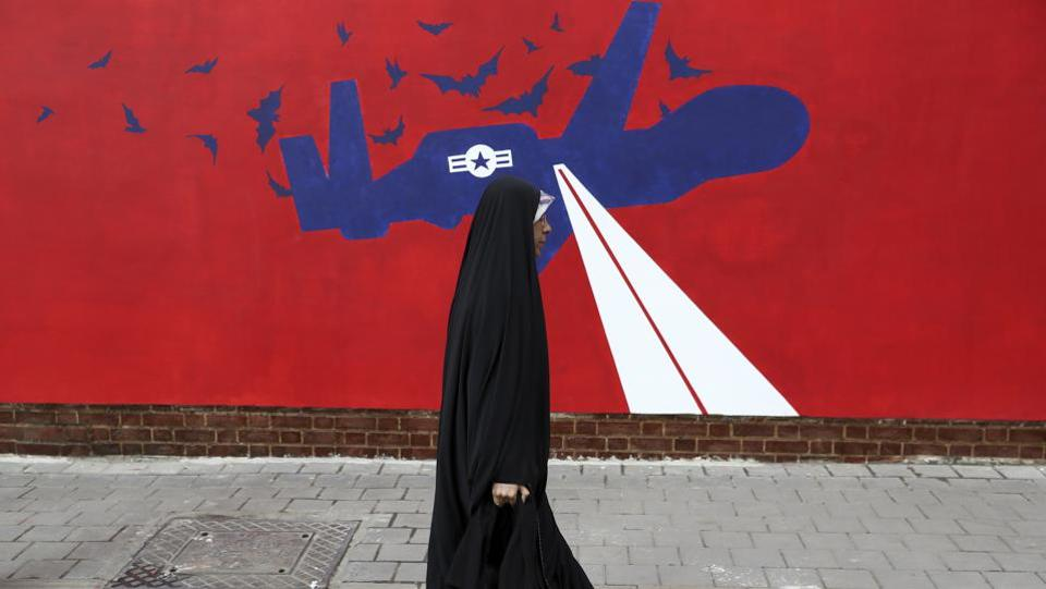 A woman walks past a new anti-U.S. mural on the wall of former U.S. embassy portraying the interception of Global Hawk US drone by Iran in Persian Gulf, after an unveiling ceremony in Tehran. (AP)
