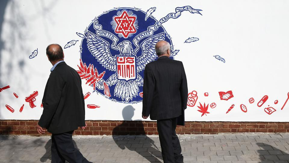 People walk in front of new murals of the former US embassy in Tehran, Iran. (VIA REUTERS)
