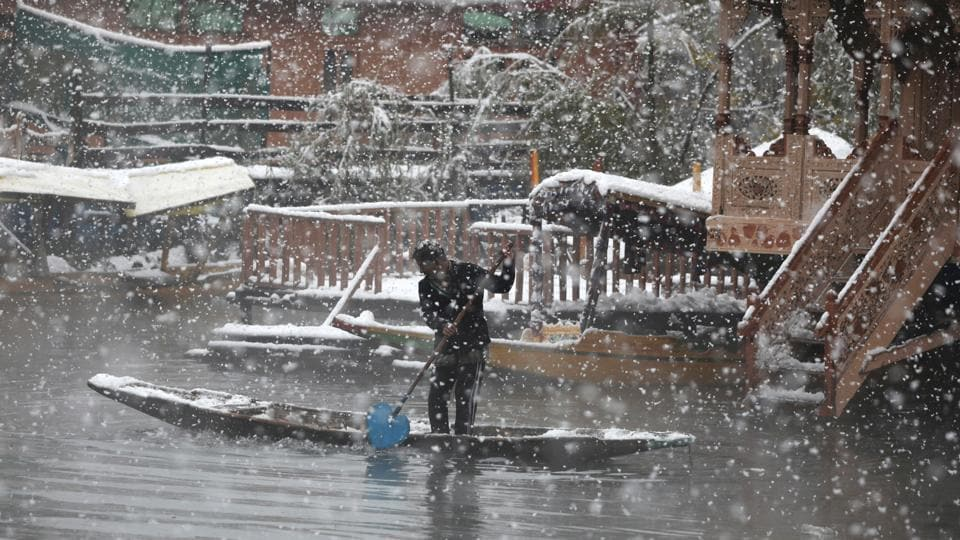 A man rows his boat as it snows in Srinagar, Jammu and Kashmir. The winds blowing from the Mediterranean Sea and their interaction with Maha Cyclone brought the first snowfall of the season in higher reaches of Kashmir on Wednesday, bringing down the temperature across the Himalayan Valley. (Waseem Andrabi / HTPhoto)