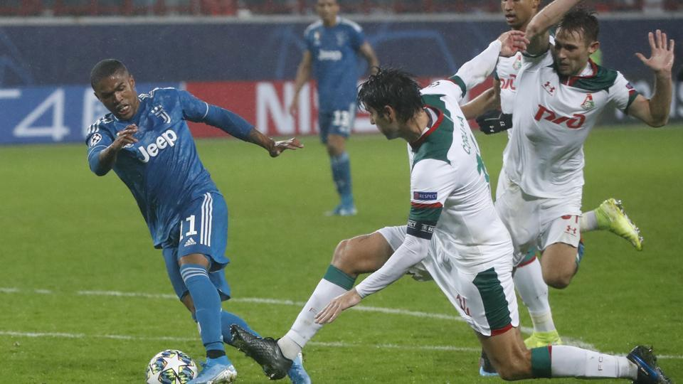 Juventus' Douglas Costa, left, fights for the ball with Lokomotiv's Vedran Corluka during the Champions League Group D soccer match between Lokomotiv Moscow and Juventus at the Lokomotiv Stadium in Moscow, Russia, Wednesday, Nov. 6, 2019.
