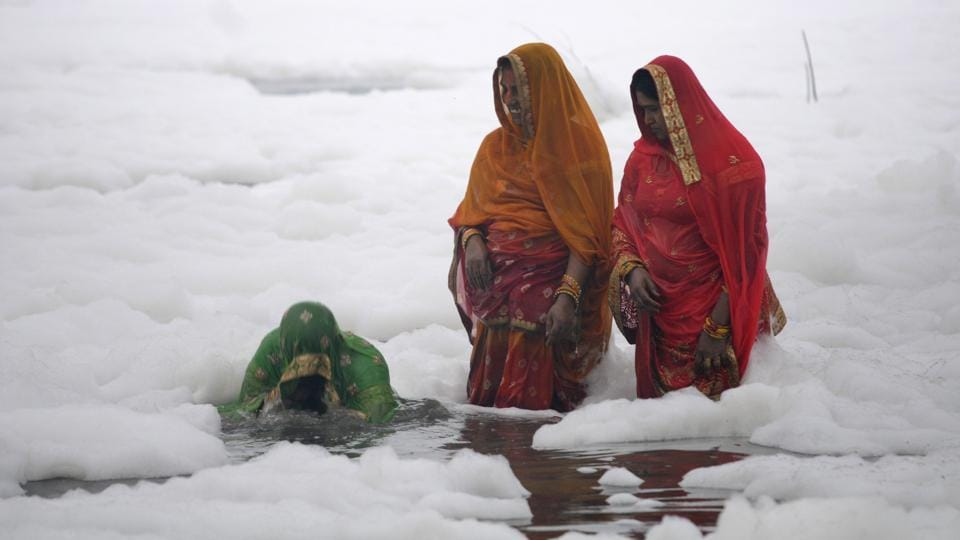 Devotees perfrom rituals in the polluted waters of Yamuna river at Kalindi Kunj on the occasion of Chhath Puja. Recently, scores of helpless devotees were forced to offer prayers to the sun god by immersing themselves in the toxic foam present inside the river Yamuna during the 4-day long Chhath Puja festival. (Sunil Ghosh / HT Photo)