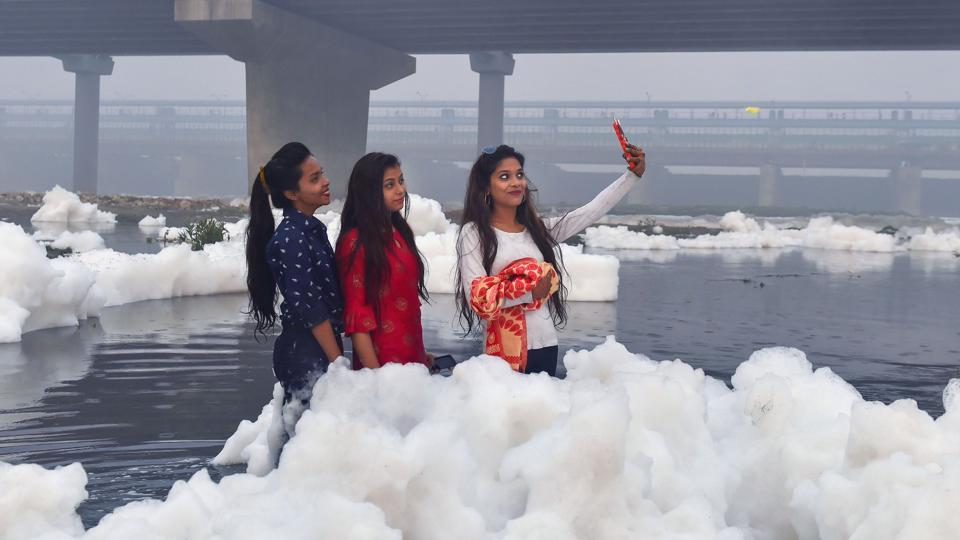 Women pose for a selfie as toxic foam floats on the surface of the polluted river. There are no fishes in the Yamuna due to lack of oxygen. Yamuna fulfills three-quarters of the capital's water needs. Several polluting industrial units pollute the water of the river on a daily basis, regardless of the fact.  (Manvender Vashist / PTI)