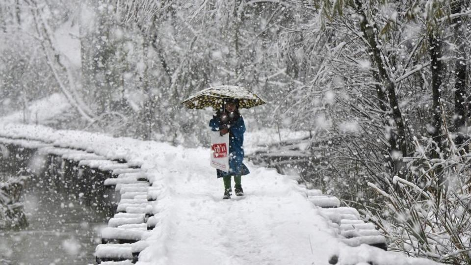 A girl walks on a snow covered foot bridge during the first snowfall of the season in the interiors of Dal Lake, Srinagar, Jammu and Kashmir, India (Photo by Waseem Andrabi / Hindustan Times)