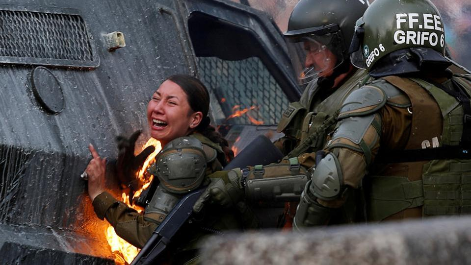 A riot police officer on fire reacts during a protest against Chile's government in Santiago, Chile. (Jorge Silva / REUTERS)