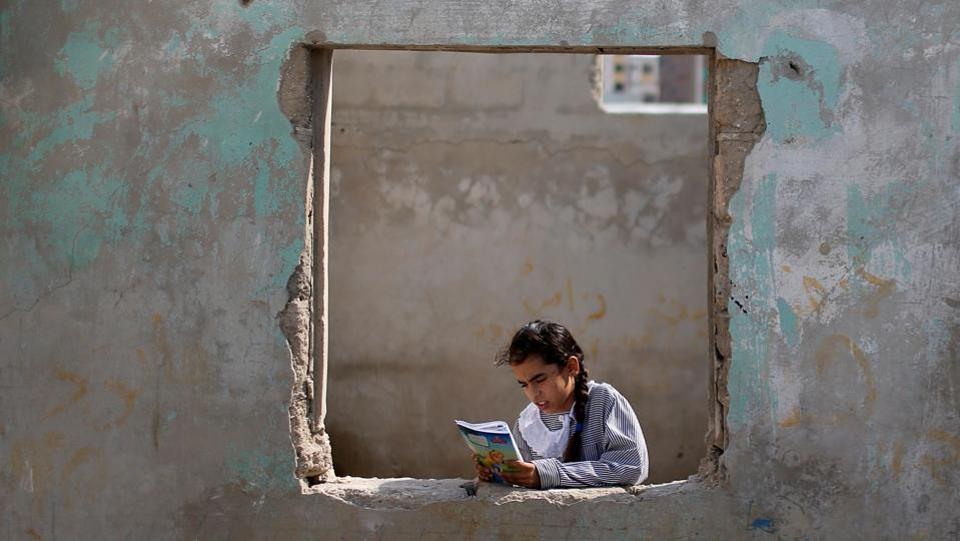 A Palestinian UNRWA schoolgirl holds her book as she stands by a window outside her family home in Al-Shati refugee camp in Gaza City. (Mohammed Salem / REUTERS)