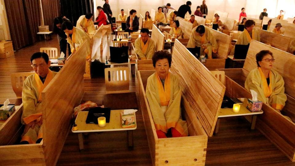 "Participants sit inside coffins during a ""living funeral"" event as part of a ""dying well"" programme, in Seoul, South Korea. (Heo Ran / REUTERS)"