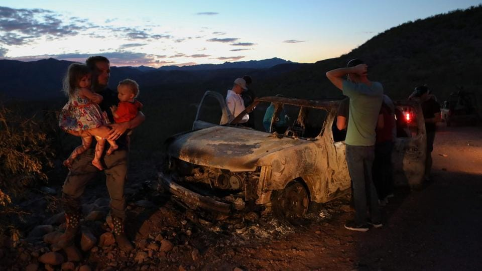 Members of the LeBaron family look at the burned car where part of the nine murdered members of the family were killed and burned during an ambush in Bavispe, Sonora mountains, Mexico, on November 5. (Herika Martinez / AFP)