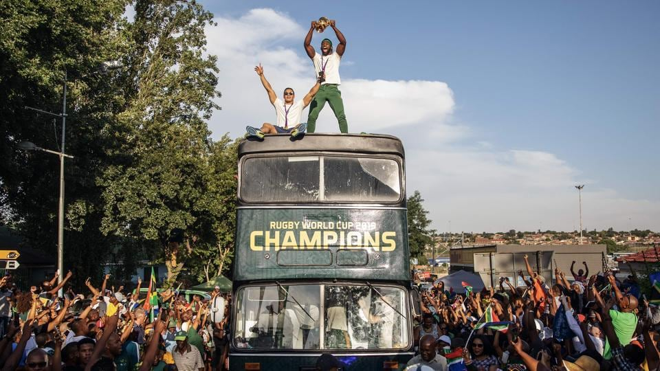 South African Rugby captain Siya Kolisi (C) holds up the Web Ellis trophy as the World Cup winner team parades Vilakazi street in Soweto on an open top bus in Soweto, South Africa.  (Michele Spatari / AFP)