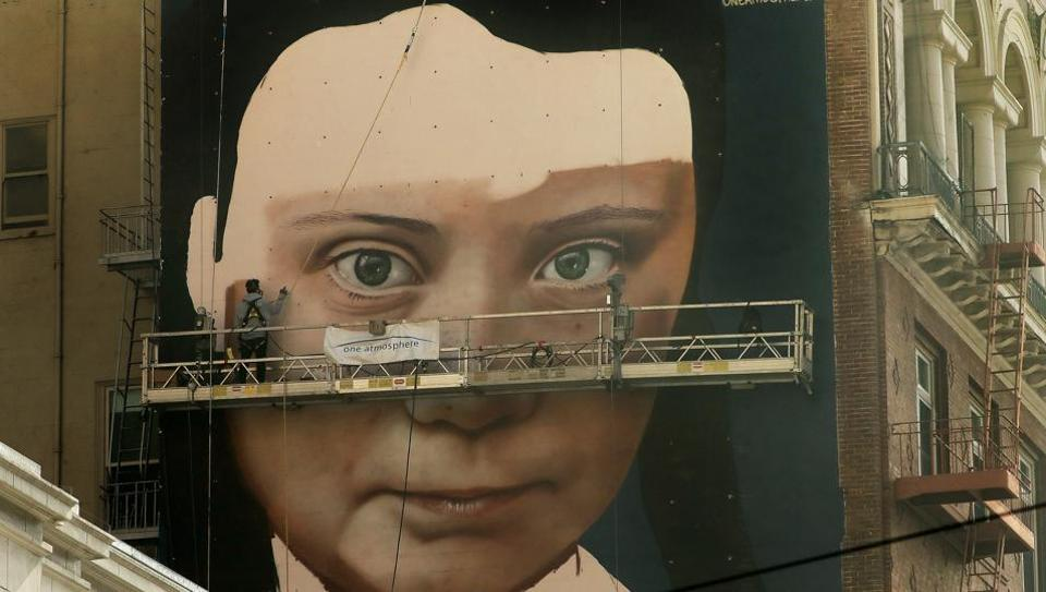 Andres Petreselli paints a mural on the side of a building depicting Swedish teen climate activist Greta Thunberg in San Francisco.