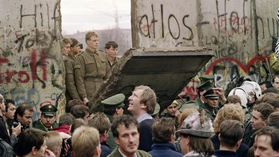 West Berliners in front of the Berlin Wall as the East German border guards demolish a section of the wall to open a new crossing point between East and West Berlin, near the Potsdamer Square, in Berlin. Germany on Saturday marked the 30th anniversary of the fall of the Berlin Wall that separated East and West Germany, with President Frank-Walter Steinmeier thanking Eastern European neighbours for enabling a peaceful revolution. (Gerard Malie / AFP File)